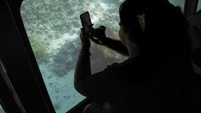 Senior female adult tourist on board a submarine for viewing coral reefs of the seabed photographs fish on a smartphone. `s chamber. Slow Motion stock video footage