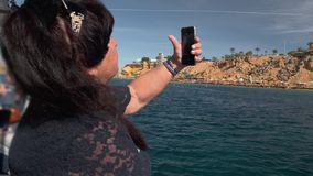 Senior female adult tourist on a boat near a tropical island uses a smartphone to talk on video communication. The. Concept of a senior age blogger. Slow Motion stock video