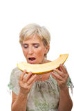 Senior female biting melon royalty free stock photo