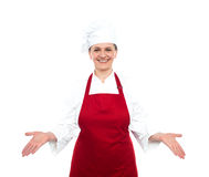 Senior female chef standing with open palms Royalty Free Stock Images