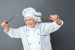 Senior woman chef studio standing isolated on gray holding knives scary smiling playful close-up stock photo