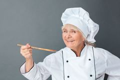 Senior woman chef studio standing isolated on gray holding spatula trying dish looking camera playful close-up. Senior female chef studio standing isolated on stock photo