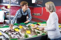 Senior female customer choosing and buying fish Royalty Free Stock Photography