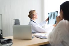 Senior Female doctor examining and looking to X-ray film. royalty free stock photography