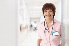 Senior female doctor in hospital smiling Stock Image