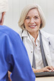 Senior Female Doctor With Male Patient. A senior female women doctor sitting at a desk wearing a suit and stethoscope talking to an elderly male patient stock images