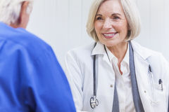 Senior Female Doctor With Male Patient. A senior female women doctor sitting at a desk wearing a suit and stethoscope talking to an elderly male patient stock photo