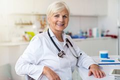 Senior female doctor smiling at the camera royalty free stock image
