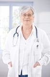 Senior female doctor smiling at hospital corridor Stock Photos