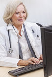 Senior Female Doctor With Stethoscope at Desk & Computer Stock Images
