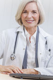 Senior Female Doctor With Stethoscope at Desk & Computer Stock Photography