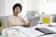 Senior Female Doctor Working At Laptop In Office Stock Photos