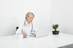 Senior female doctor writing notes while looking at laptop in clinic Royalty Free Stock Photo
