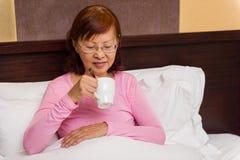 Senior female drinking tea Stock Images