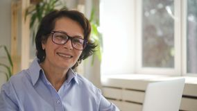 Senior female editor in glasses and blue shirt smiling stock footage