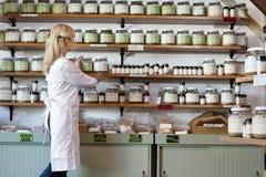 Senior female employee arranging spice jars on shelf Stock Photos