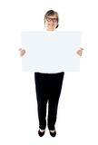 Senior female executive showing advertising board Stock Photo
