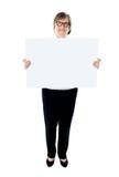 Senior female executive showing advertising board Stock Photo