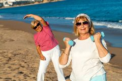 Senior female fitness session on beach. Royalty Free Stock Image