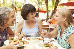 Senior Female Friends Eating Meal In Outdoor Restaurant Stock Photo