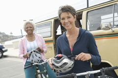 Senior Female Friends Holding Cycling Helmets Stock Photos