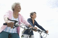 Senior Female Friends Riding Bicycles Stock Images
