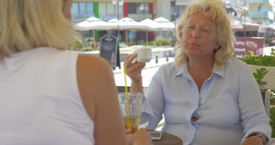 Senior female friends talking in street cafe stock video