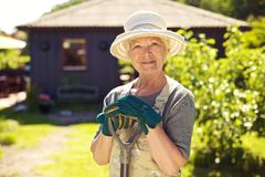 Senior female gardener in backyard with shovel Royalty Free Stock Photography