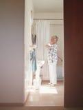 Senior female getting ready in bathroom Royalty Free Stock Image