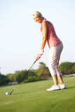 Senior Female Golfer Teeing Off