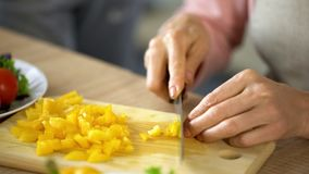 Senior female hands cutting fresh yellow pepper, cooking healthy family lunch stock photo