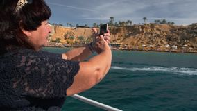 Senior female happy adult tourist resting on a yacht photographs a sailing boat with unrecognized tourists on the stock footage