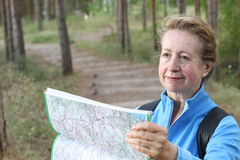 Senior female looking at map and planning trip or get lost in the dark woods Royalty Free Stock Photo