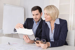 Senior female managing director with her assistant looking in a Stock Image