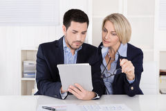 Senior female managing director with her assistant looking in a Stock Images