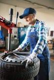 Senior female mechanic repairing a car in a garage. Stock Images