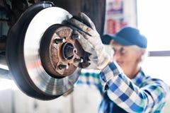 Senior female mechanic repairing a car in a garage. Royalty Free Stock Photos