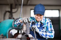 Senior female mechanic repairing a car in a garage. Female mechanic repairing a car. A senior woman working in a garage Royalty Free Stock Photos