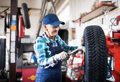 Senior female mechanic repairing a car in a garage. Female mechanic repairing a car. A senior woman working in a garage Royalty Free Stock Photo