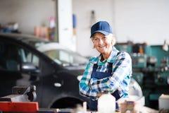 Senior female mechanic repairing a car in a garage. Stock Image