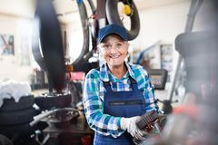Senior female mechanic repairing a car in a garage. Royalty Free Stock Photography