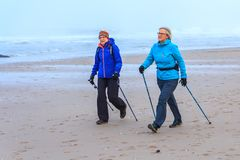 Senior female nordic walkers exercising on the beach. Kijkduin beach, The Hague, the Netherlands - 2 December 2017: senior female nordic walkers exercising on Royalty Free Stock Photography