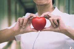 Senior female nurse holding red heart with love. For Valentine`s day royalty free stock photo