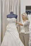 Senior female owner adjusting wedding dress on mannequin in bridal store Stock Images