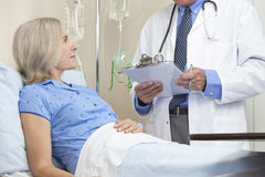 Senior Female Patient Hospital Bed & Male Doctor. Senior women in a hospital bed having talking to male doctor with stethoscope and clipboard Royalty Free Stock Photos