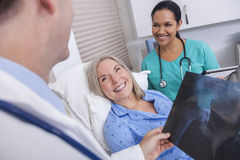 Senior Female Patient With Nurse and Male Doctor. A happy senior female women elderly patient in bed looking at X-ray with male doctor and Hispanic nurse Royalty Free Stock Images