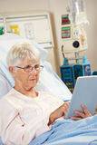 Senior Female Patient Relaxing In Hospital Bed Stock Photography