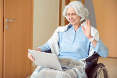 Senior female patient using laptop. Hay. Positive and happy woman sitting in wheelchair and using laptop and webcam Royalty Free Stock Photos