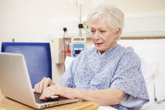 Senior Female Patient Using Laptop In Hospital Bed Royalty Free Stock Image
