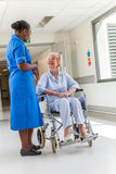 Senior Female Patient in Wheelchair & Nurse in Hospital. Senior female women patient in wheelchair sitting in hospital corridor with African American female Royalty Free Stock Photos